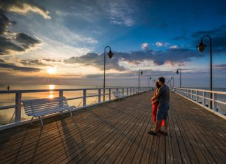 Apartamenty Gdynia – para zakochanych na molo podziwia zachód słońca