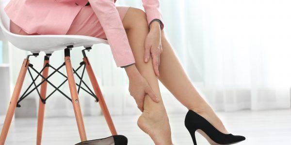 Zakrzepica - kobieta trzymająca się za bolącą łydkę.